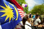 Many countries and world cultures were on display at UNCG's 30th International Festival held on April 14, 2012. Malaysian flags blow in the wind as visitors line up to taste a sample of Malaysian food. (UNCG Photo/Chris English)