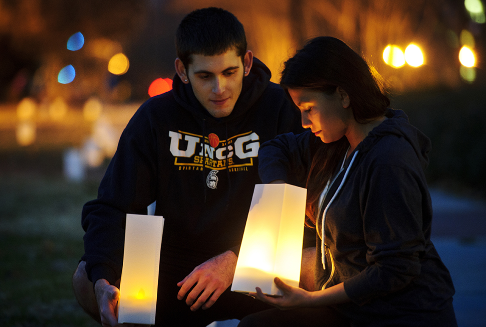 UNCG students Travis Webster, left, and Mary Rizkalla place luminaires on College Avenue. (Chris English/UNCG Photo)