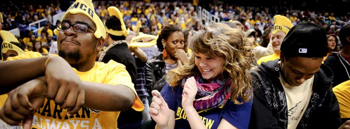 Members of the UNCG Blue Crew cheer on the Spartans as they take on Elon University at the Greensboro Coliseum.