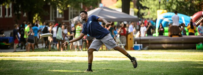 UNCG student Nebraska Wiggins throws the frisbee at the Quad during the Residence Life Carnival.